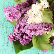 Beautiful lilac flowers, on color wooden background — Stock Photo #27368119