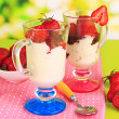 Delicious strawberry desserts in glass vase on wooden table on natural background — Lizenzfreies Foto