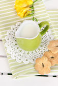 Green jug with milk and cookies on wooden picnic table close-up — Stock Photo