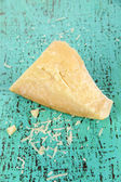 Piece of Parmesan cheese on wooden blue table close-up — Stock Photo