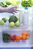 Woman's hand reaching out for food from the refrigerator, close up — Stock Photo