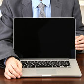 Young businessman with laptop computer facing on his workplace — Stock Photo