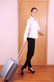 Young businesswoman with suitcase leaving room — Stock Photo