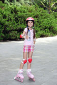Little girl in roller skates drinking water at park — Stock Photo