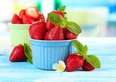 Dulces fresas en tazones en tabla de madera azul — Foto de Stock