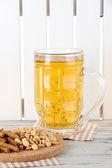 Pivo v skleněných drtí a ořechy na ubrousek na stůl na plot pozadí — Stock fotografie