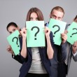 Foto Stock: Business team standing in row with question mark on grey background