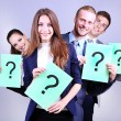 Business team standing in row with question mark on grey background — Stock Photo