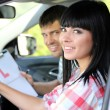 Beautiful young woman taking driving lesson — Stock Photo #27375609