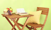 Wooden table with fruit and book on it on green background — Stock Photo