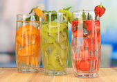 Glasses of fruit drinks with ice cubes on table in cafe — ストック写真