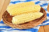 Fresh corn on wicker mat, on wooden background — Stock Photo
