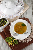 Cup of tea with linden on napkins on wooden table — Stock Photo