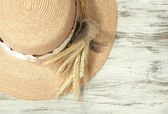 Beautiful summer hat with spikelets on wooden background — Stock Photo