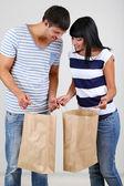 Beautiful loving couple is shopping on grey background — Stock Photo