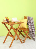 Wooden table with fruit and book on it in room — Stock Photo