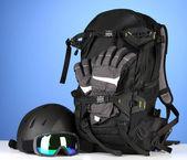 Winter sport glasses, helmet and gloves, backpack, on blue background — Stock Photo