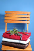Towels and flowers on wooden chair on blue background — Stock Photo