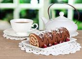 Söt rulle med kopp te på bordet i rummet — Stockfoto