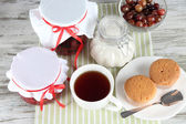 Yummy jam in banks on napkin on wooden table — Stock Photo