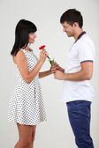 Beautiful loving couple with rose on grey background — Stock Photo