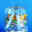 Glass jar containing various colored ribbons on blue background — Stock Photo