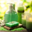 Cosmetics bottles and natural handmade soap on green background — Стоковая фотография