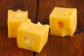Cheese cubes on wooden table — Zdjęcie stockowe
