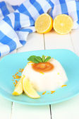 Lemon Panna Cotta with orange zest and caramel sauce, on color wooden background — Stock Photo