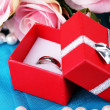 Stock Photo: Rose and engagement ring on blue cloth