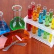 Test tubes with colorful liquids on wooden background — Stock Photo