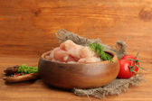 Raw chicken meat in bowl, on wooden background — Stock Photo