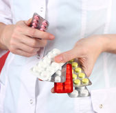 Close-up of female doctor hand holding pills, on color background — Stock Photo
