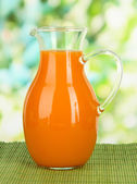 Orange juice in pitcher on table on bright background — Stock Photo
