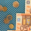Euro banknotes and euro cents on blue background — Stock Photo #27493101