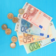 Euro banknotes and euro cents on blue background — Stock Photo #27494223