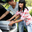 Portrait of happy beautiful couple putting suitcase into car — Stock fotografie