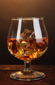 Brandy glass with ice on wooden table on brown background — Stock Photo