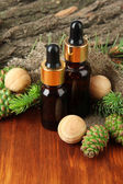 Bottles of fir tree oil and green cones on wooden table — Stock Photo