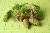 Hand-made soap and green pine cones on bamboo mat — Stock Photo