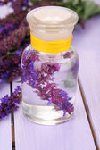 Medicine bottle with salvia flowers on purple wooden background — Stock Photo