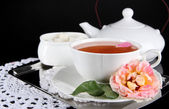 Kettle and cup of tea from tea rose on metallic tray on napkin black background — Stock Photo