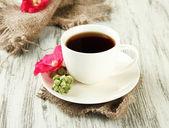 木製の背景上のコーヒーとピンク アオイ科の植物の花のカップ — ストック写真