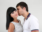 Hermosa cariñosa pareja besándose en fondo gris — Foto de Stock