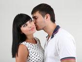 Mooie verliefde paar zoenen op grijze achtergrond — Stockfoto