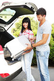 Portrait of happy beautiful couple putting suitcase into car — Stock Photo