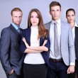 Business team standing in row on grey background — Stock Photo #27500527