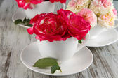Roses in cups on wooden background — Stock Photo