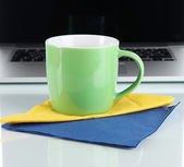 Green cup on napkin on laptop background isolated on white — Stock Photo