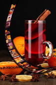 Mulled wine in glass with photographic film of drinks on black background — Stock Photo